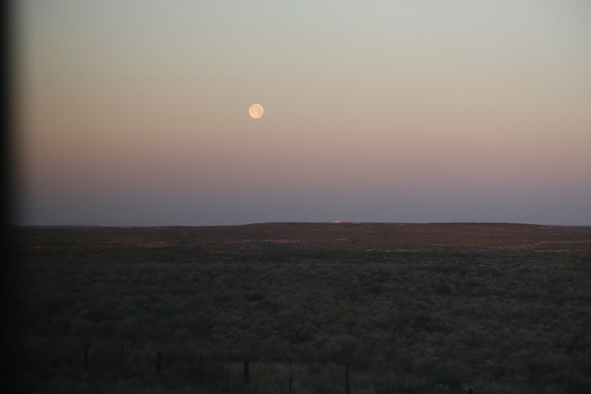 Full moon, almost sunrise and brush land