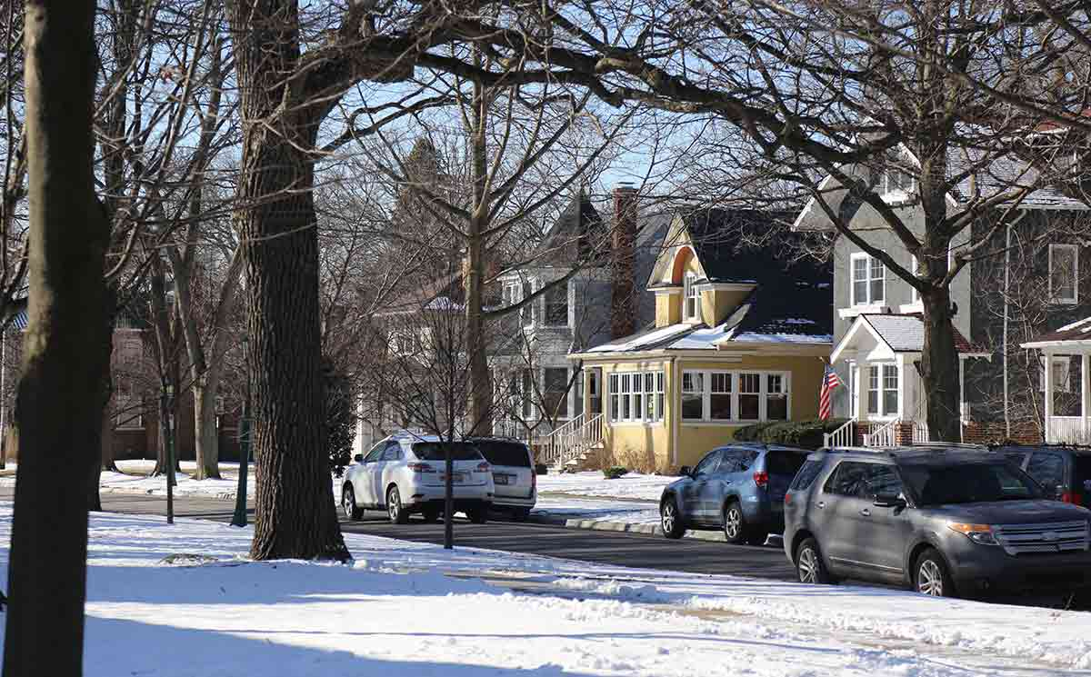 Residential street with cars, houses and trees and snow