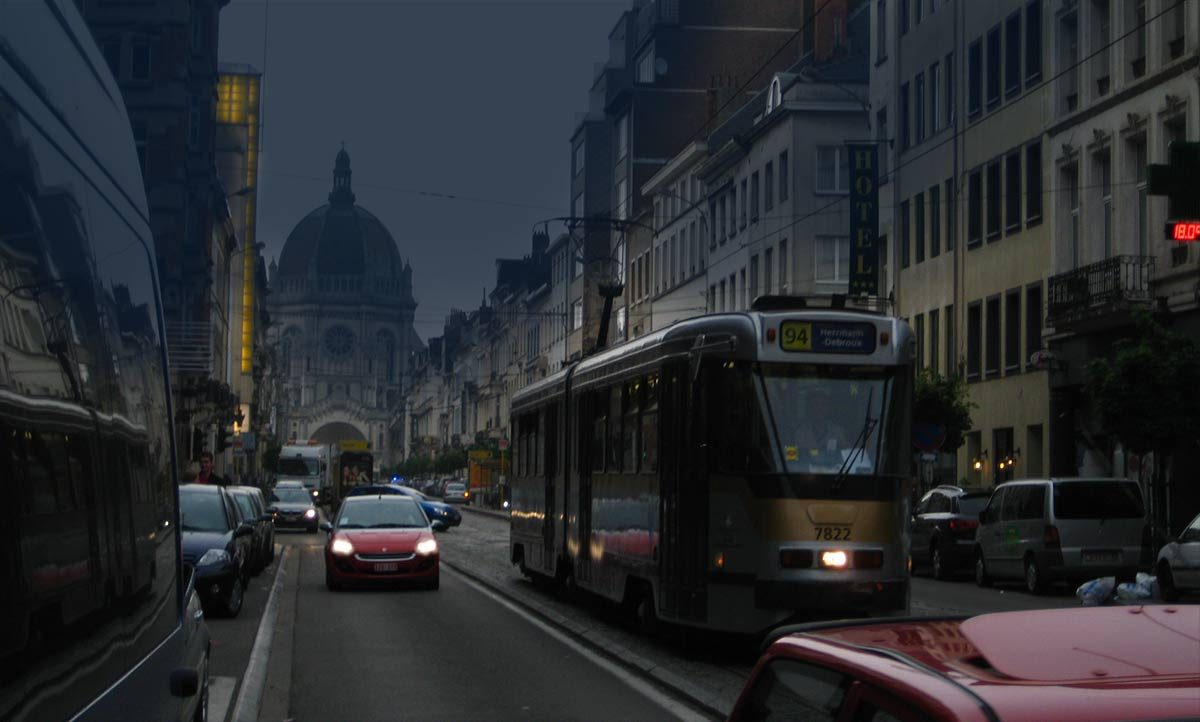 Brussels street at dusk with cars and tram