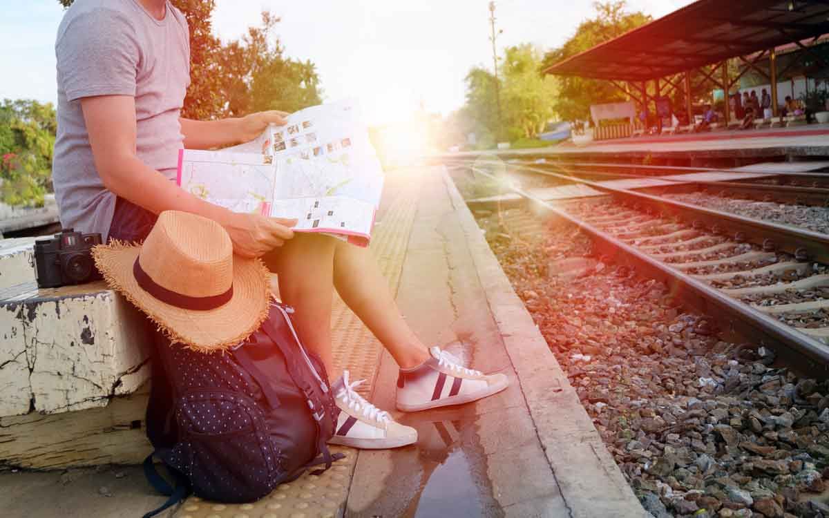 Girl sitting with her pack on a train platform looking at a map