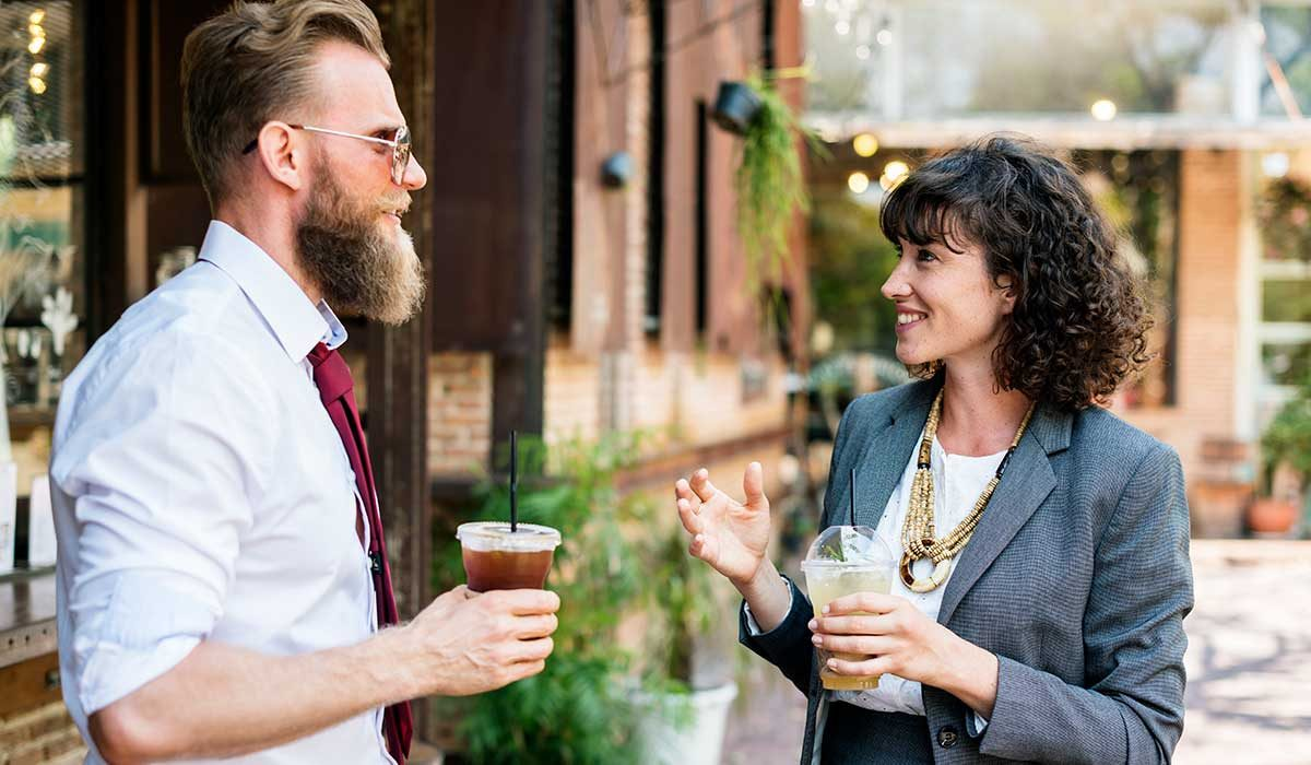 Standing man and woman engaged in active conversation that includes listening to each other