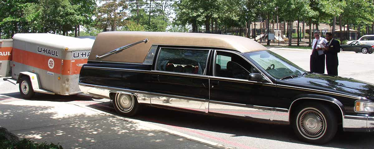 Hearse with a U-Haul trailer behind it at a funeral