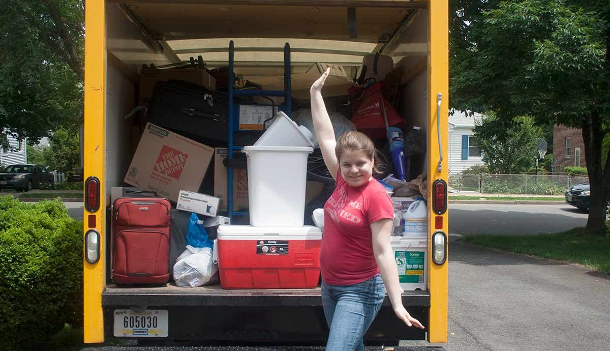 Open back of loaded moving truck, woman posing by it