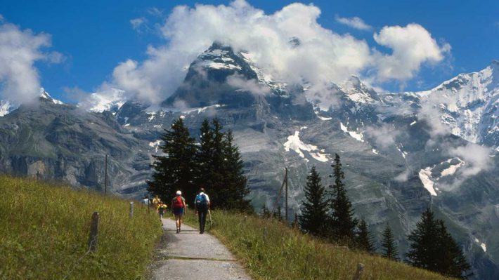 Walking path in Swiss Alps, high meadow, people walking along path, mountains in background, including the Eiger