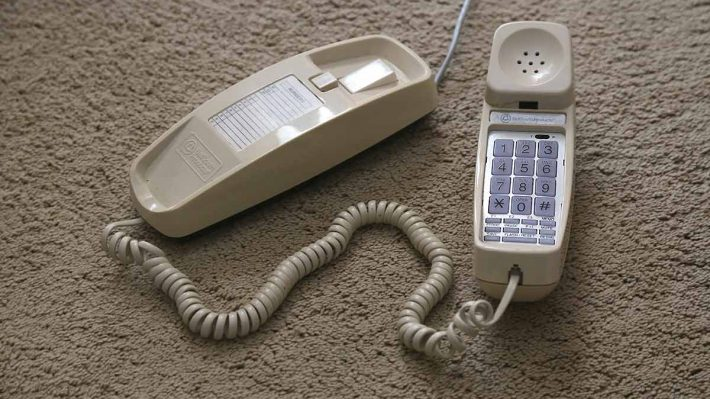 trimline style phone on floor carpet, handset sitting next to phone base