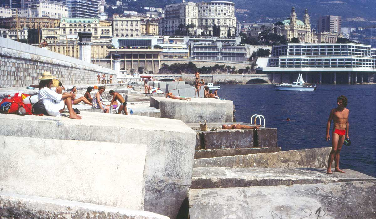 Monaco: people hanging out on the breakwater in the harbor