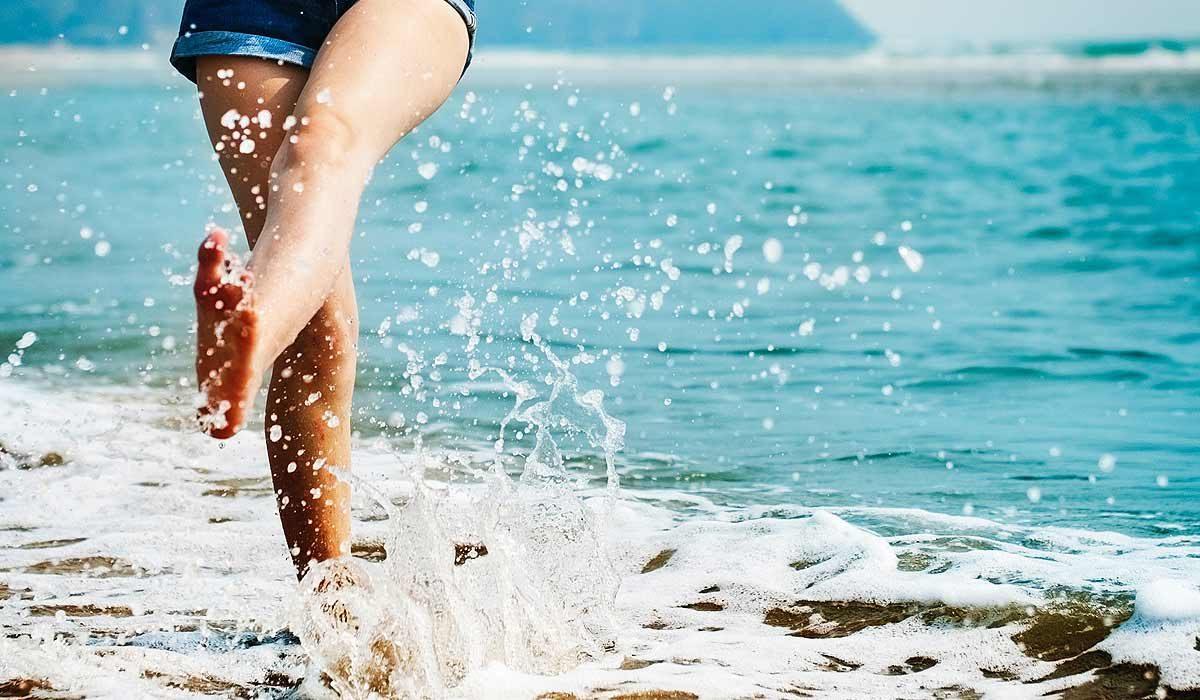 Seashore, feet splashing in the water