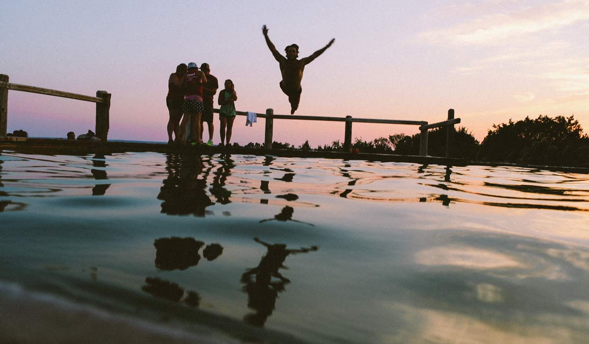 Several people standing by a pool at dusk, one person jumping into the water
