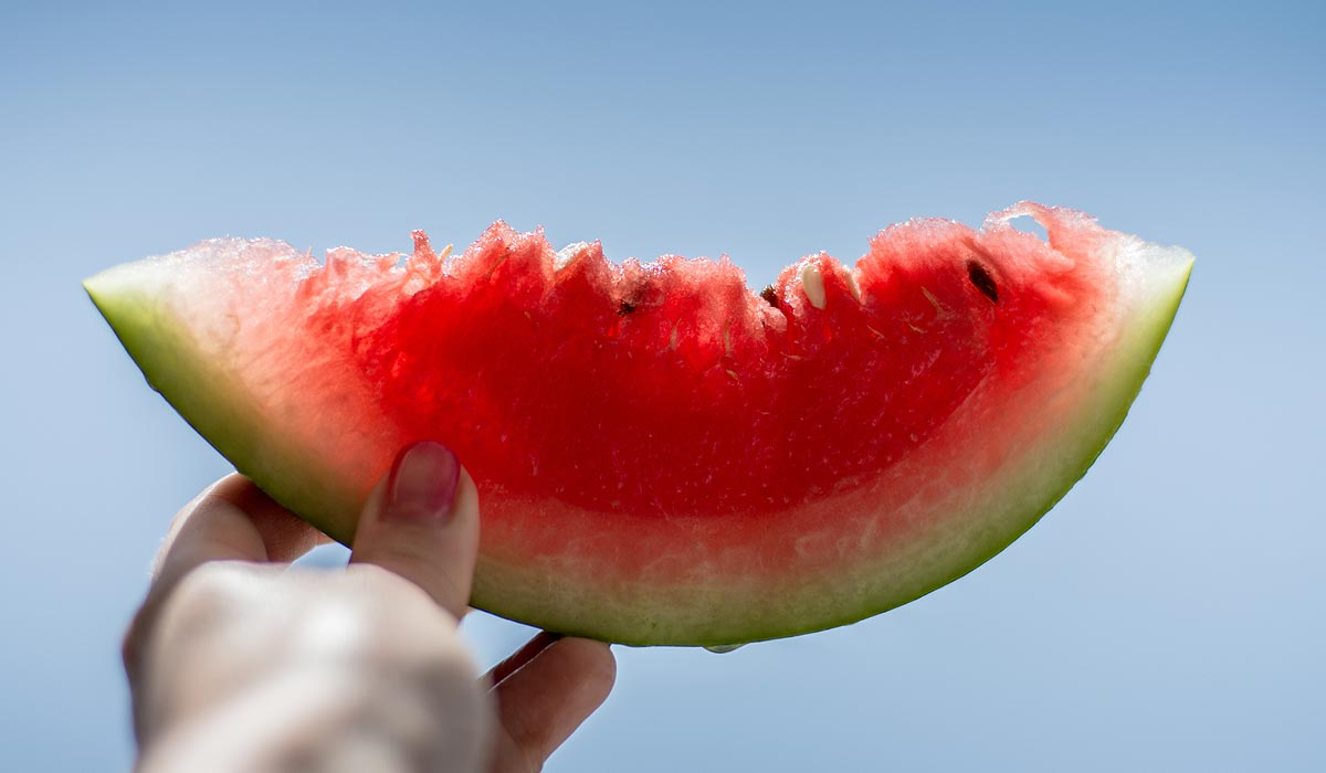 hand holding up a slice of watermelon against blue sky