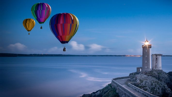 3 balloons over sea, lighthouse in foreground