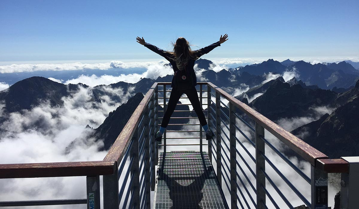 Woman with backpack and arms outstretched on observation platform high up in mountains