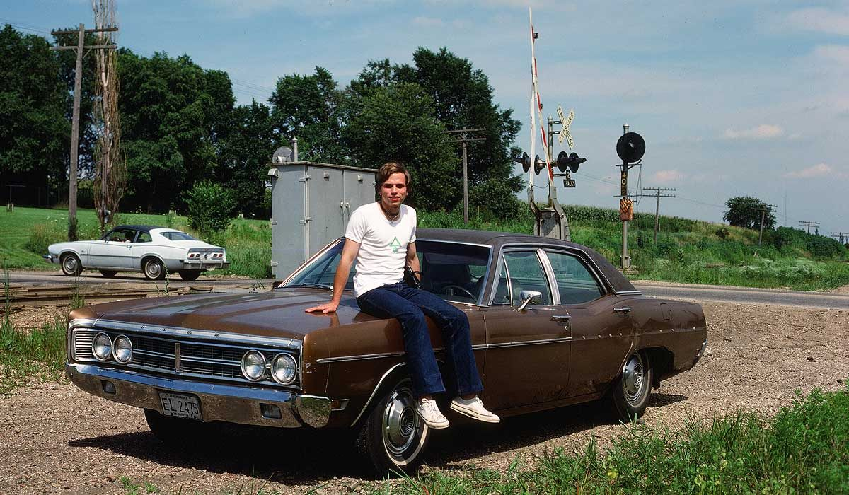 Claes sitting on the hood of a big old car. Photo from 1978.