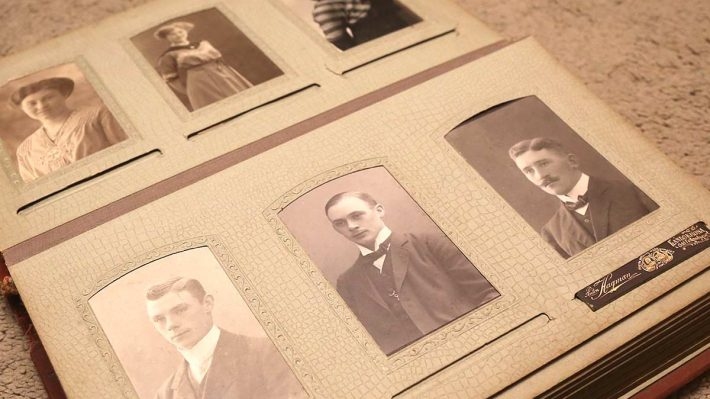 Old photo album with pictures of men and women