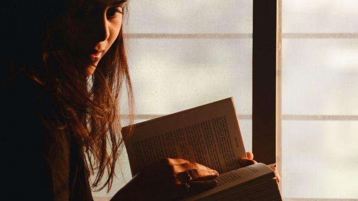 Woman sitting in window, reading a book and looking towards camera