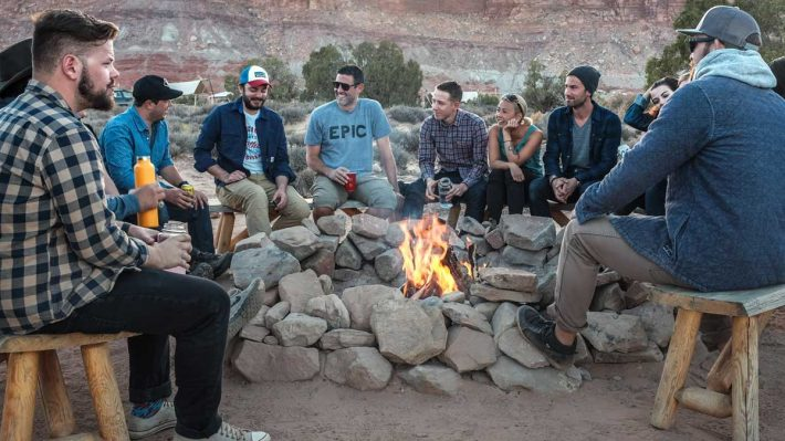 Group of men and women around campfire talking