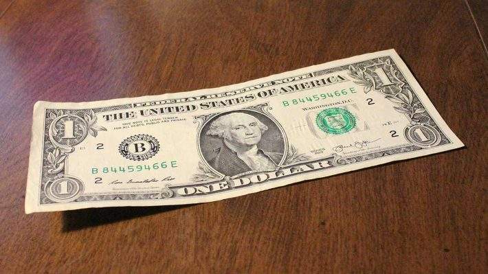 One dollar bill sitting on table top