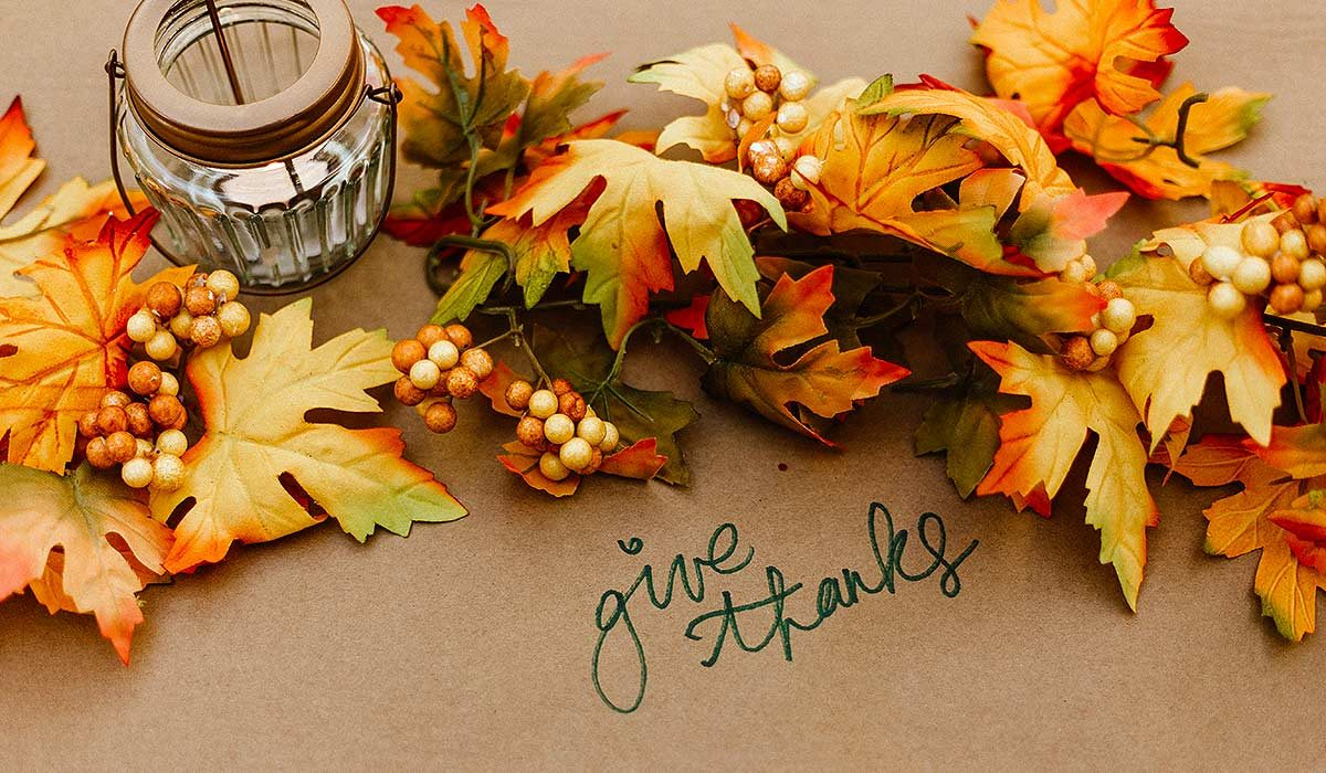 "Leaves in fall colors, a candle, berries and the words ""Give thanks"" written on the table"