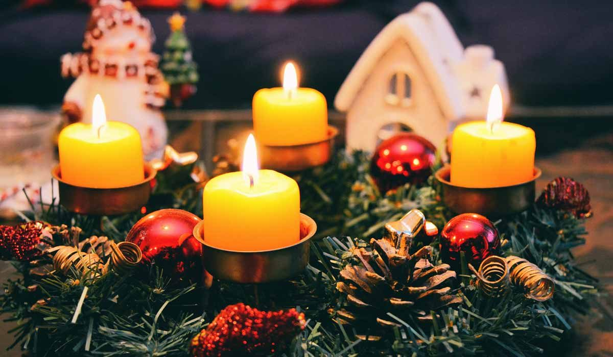 Arrangement of a group of lit candles, Christmas greenery, a miniature house and a snowman figure