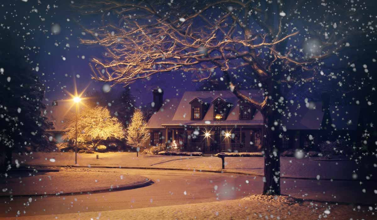 postcard like scene of snow-covered street, house and streetlight at night, with snow falling
