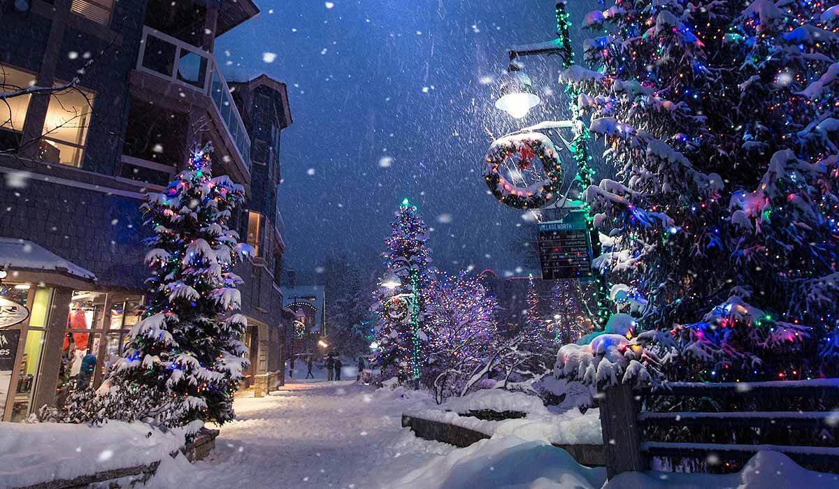 Street in village at Christmas - lights, decorations, snow on ground and falling