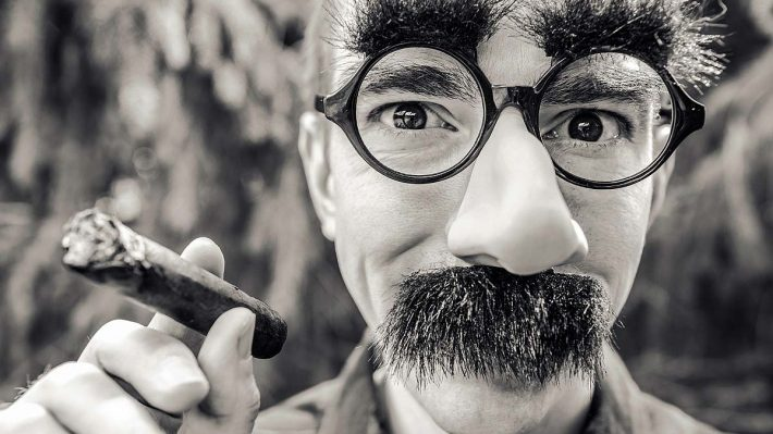 Face hidden behind Groucho Marx mask