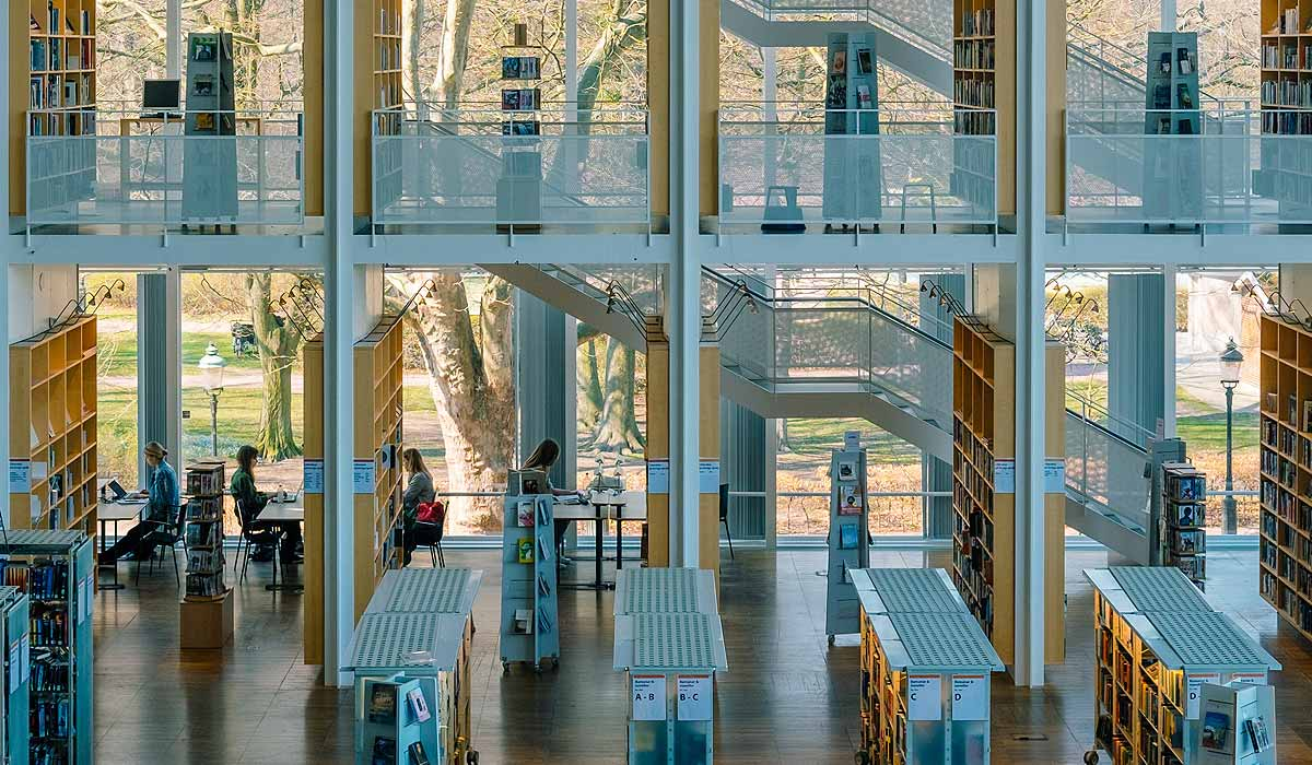 Multi-story library with book stacks, people reading at desks, all against a big glass wall.