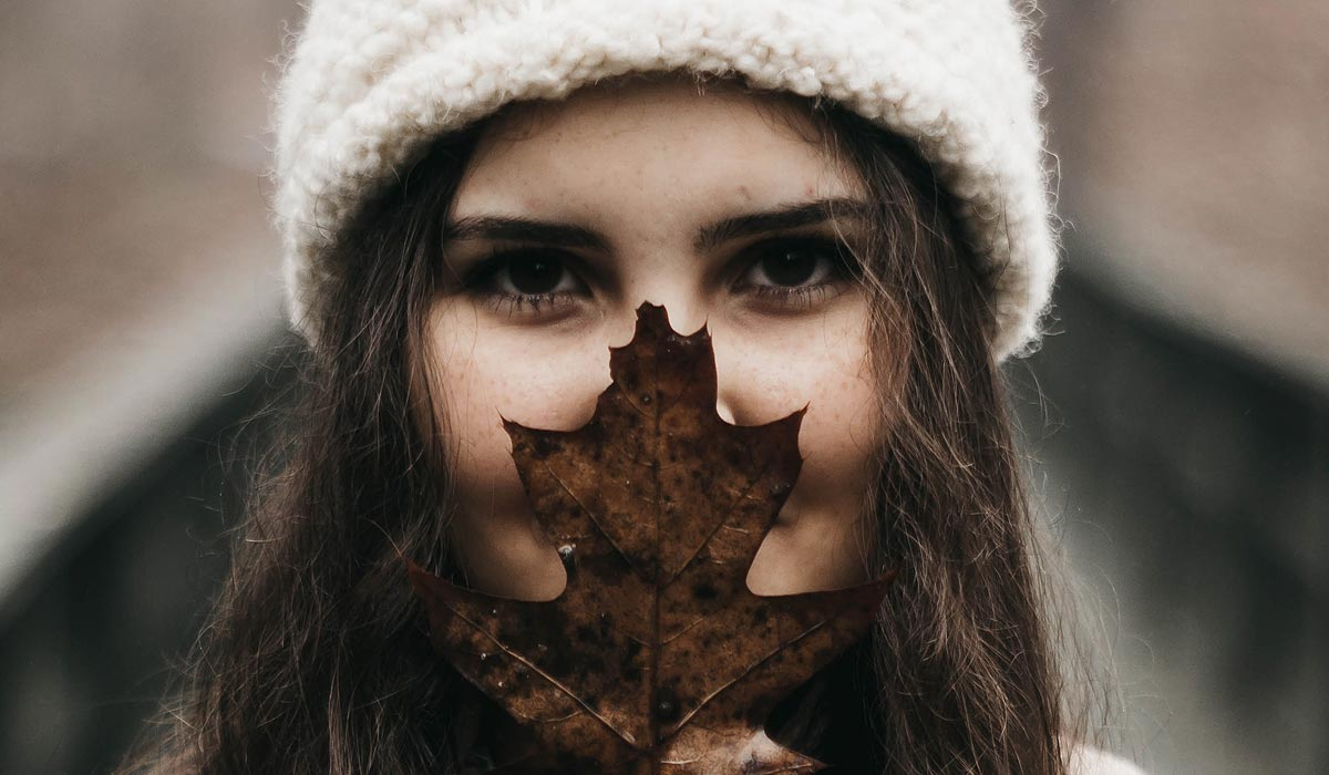 Woman, much of face hidden behind big leaf