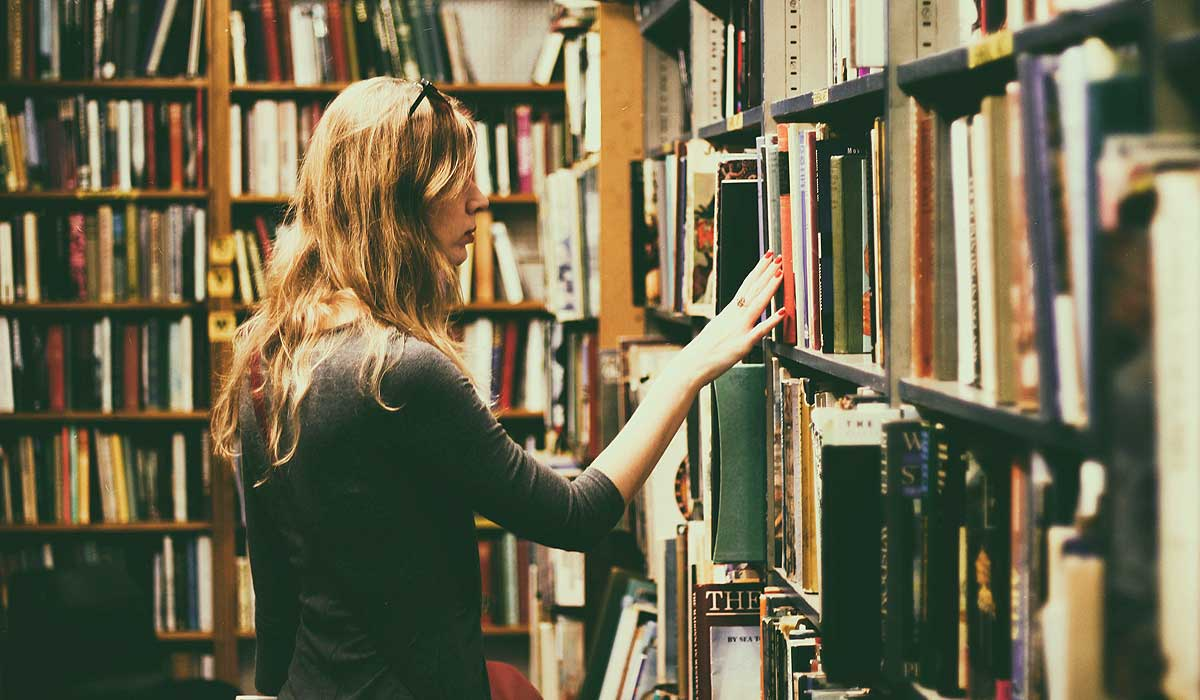 Woman perusing book shelves in library