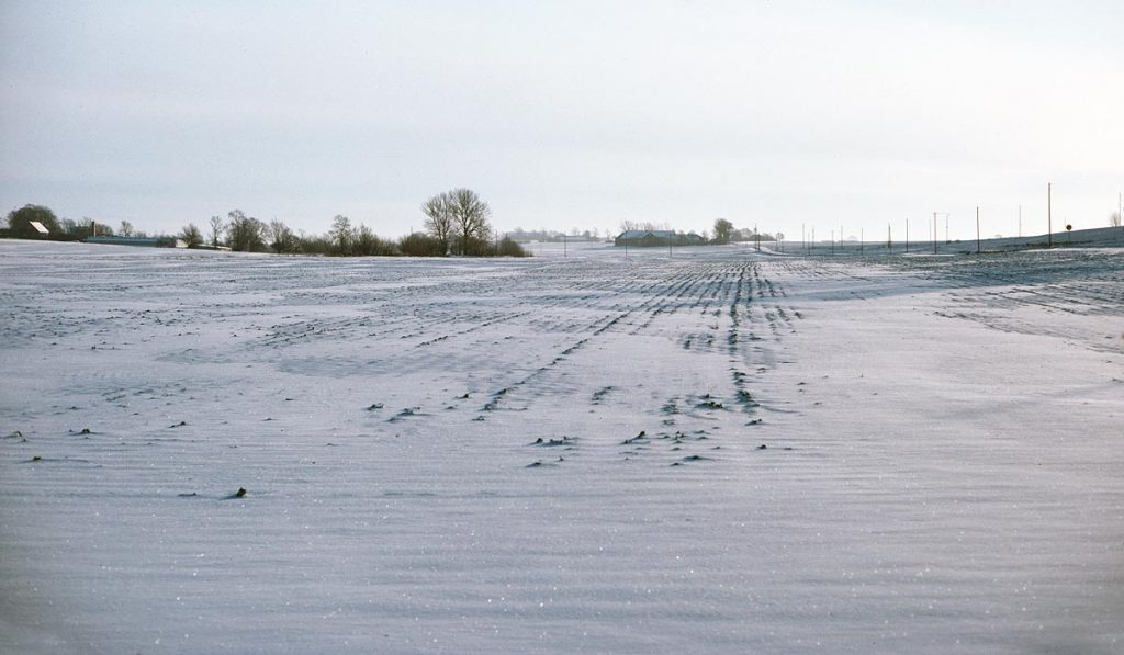 Snow covered farm fields with farms on the horizon on a sunny winter day in southern Sweden