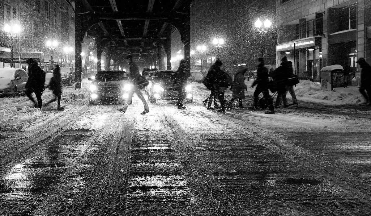 Winter city street, people crossing in snow and slush