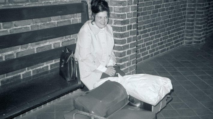 woman on bench at train station with lots of luggage