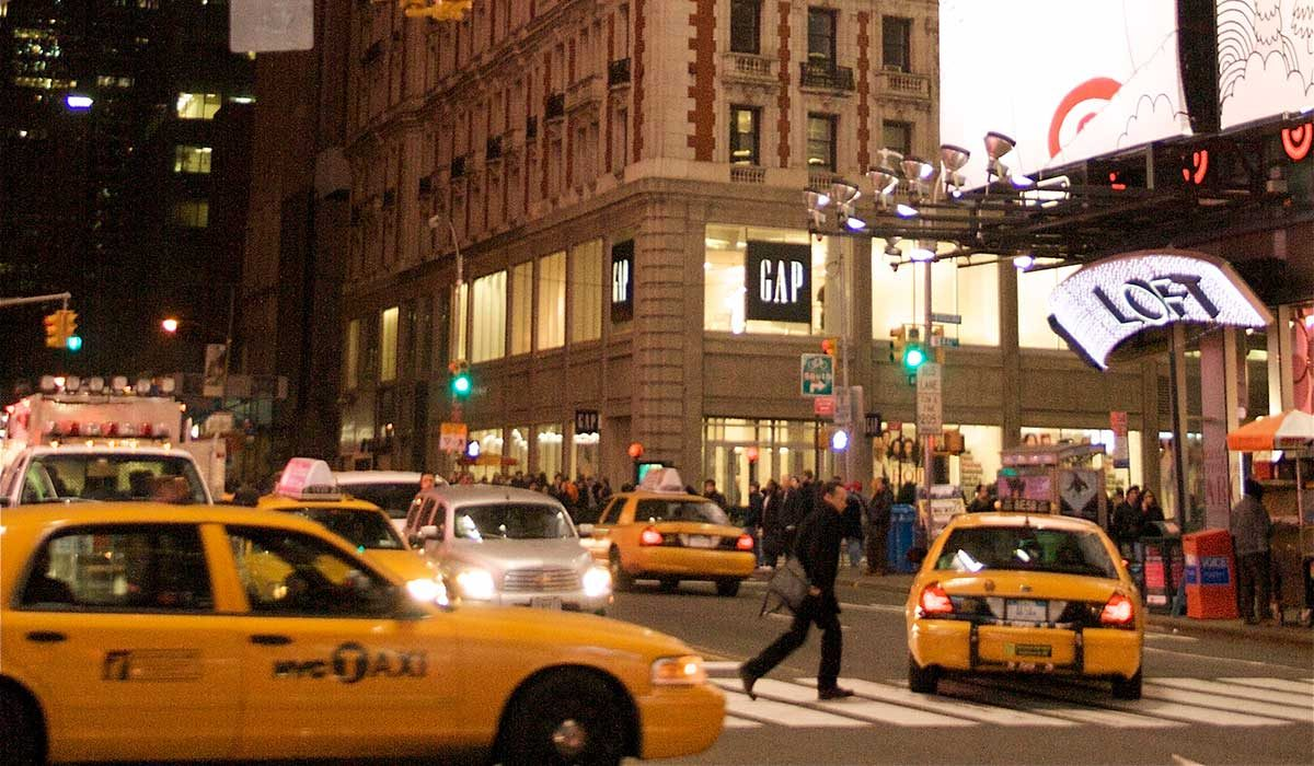 New York street at night with several taxis and other cars