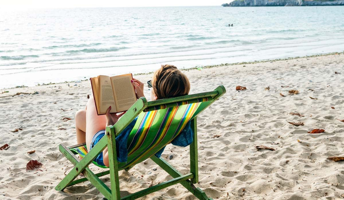 Woman reading a book, sitting in a folding chair on a beach by the sea