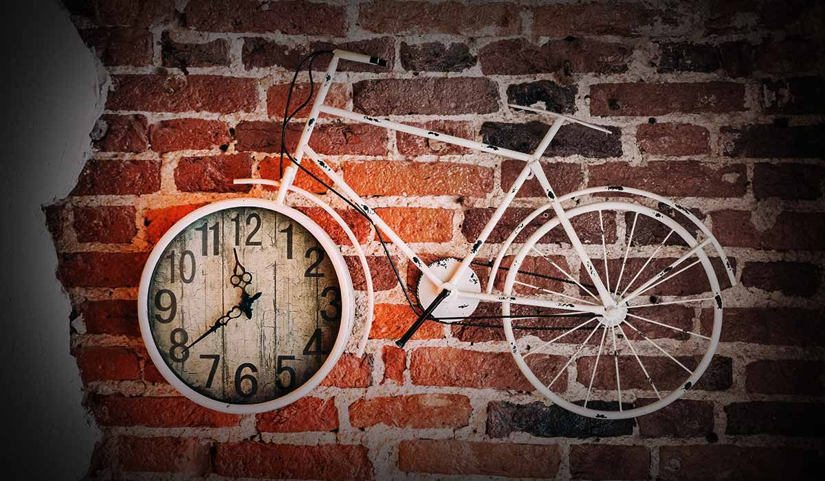 Brick wall with bicycle on it. Front wheel is a clock.