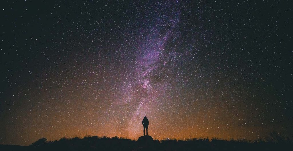 night sky: person silhouetted against stars and Milky Way