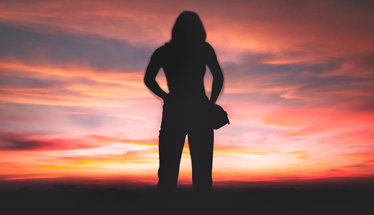 Silhouette of woman against red sky