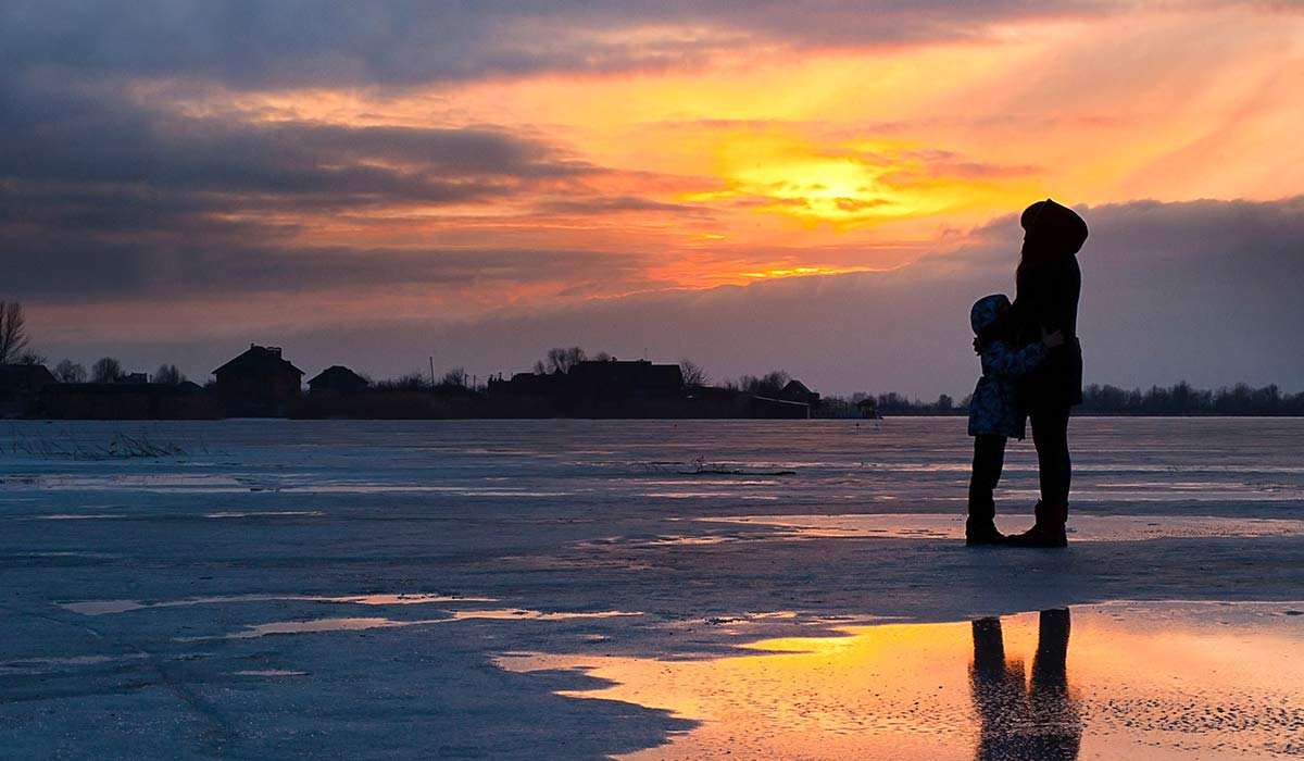 woman and child on icy field as sun rises in winter