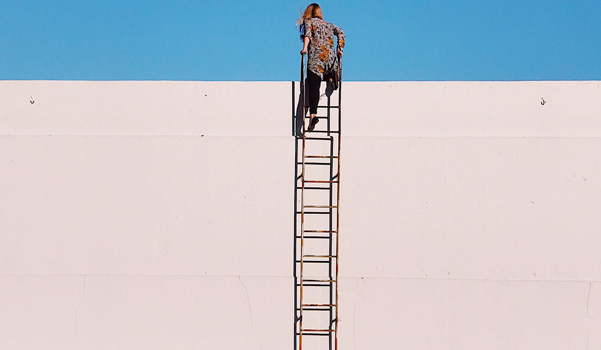 woman climbing a ladder to top of wall