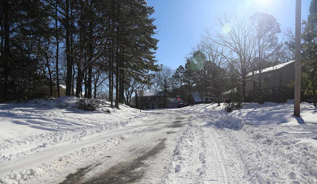 sunshine, snow on ground, houses and trees