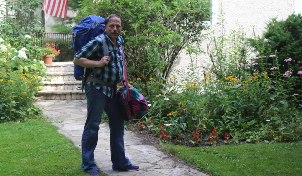 Claes with backpack in front yard
